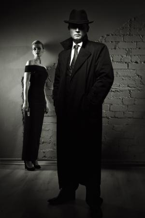 hombre con sombrero: El cine negro. Detective hombre con una gabardina y un sombrero y una mujer peligrosa con una pistola en la mano Foto de archivo