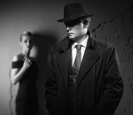 mystery woman: Film noir. Detective man in a raincoat and hat and a dangerous woman with a gun in his hand