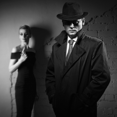 woman boss: Film noir. Detective man in a raincoat and hat and a dangerous woman with a gun in his hand