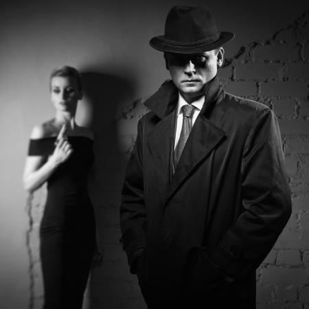 Film noir. Detective man in een regenjas en hoed en een gevaarlijke vrouw met een pistool in zijn hand