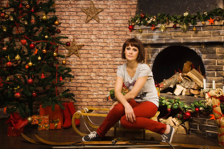 Woman posing by the fireplace with Christmas gifts Stock Photo - 25208533