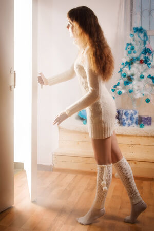 unclosed: Young girl in a wool sweater opens a magic door