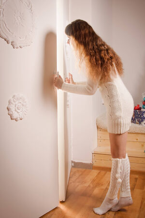 Young girl in a wool sweater opens a magic door photo