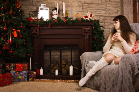 Young girl posing by the fireplace with Christmas gifts photo