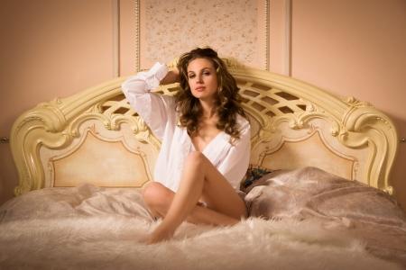 エレガントな女性が、エレガントなベッドルームでポーズ 写真素材