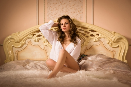 Elegant woman posing in an elegant bedroom