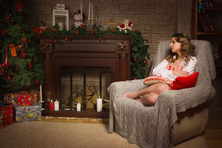 Young girl sitting in a armchair by the fireplace photo