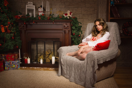 Young girl sitting in a armchair by the fireplace Stock Photo - 25310929
