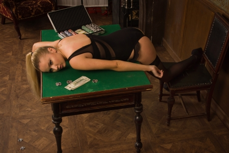 Lifeless woman in a luxurious lingerie lying on the casino table photo