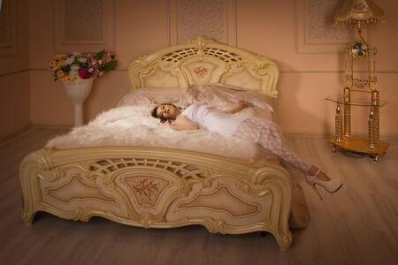 Elegant girl in evening dress posing in an elegant bedroom photo