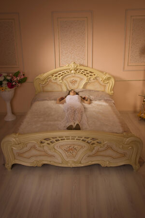 Young elegant girl lying on the bed in a luxurious interior. photo