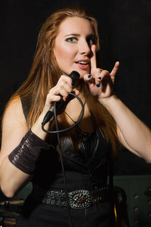 Rock star girl singing to the microphone in a studio photo