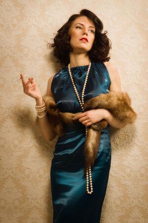 smocking: Brunette model dressed up in retro clothing smocking Stock Photo