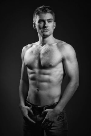 Sexual muscular man posing over dark background photo