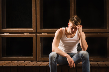 Young male sitting on floor with head down as if sad or depressed photo