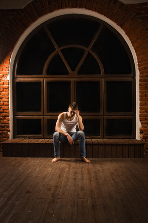 lonely man: Young male sitting on floor with head down as if sad or depressed