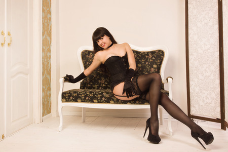 Attractive pin-up girl wearing black underwear posing on the couch photo