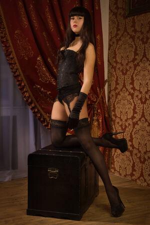 Fashion shoot of pin-up girl wearing black underwear in the dark interior photo