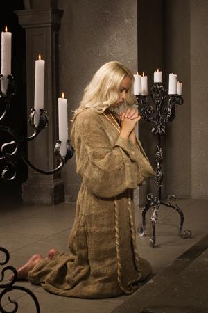 arrepentimiento: Sinner reza en la iglesia medieval Foto de archivo