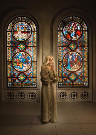arrepentimiento: Novicia joven rezando en una iglesia medieval