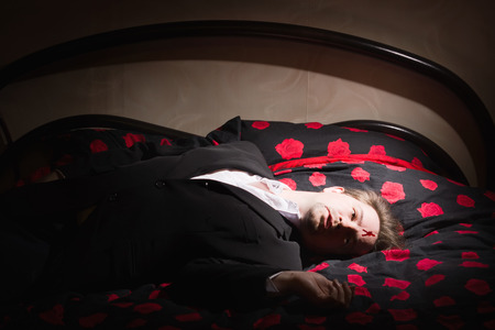 senseless: Corpse of business man lays on a bed Stock Photo