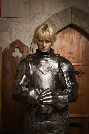 Joan of Arc. Girl in a knights armor in the interior of a medieval castle photo