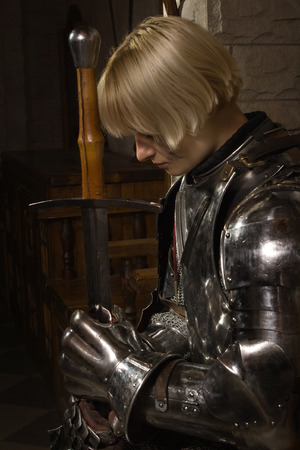 Joan of Arc. Girl in a knights armor in the interior of a medieval castle Stock Photo