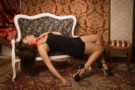 Crime scene simulation. Lifeless woman in a luxurious lingerie on the sofa photo