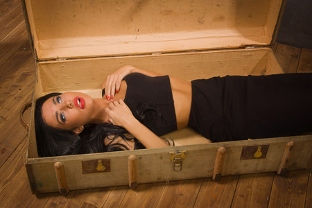 Crime scene in a vintage style. Pretty victim lying in the suit-case photo