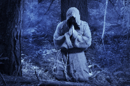 Medieval monk praying in the misty forest