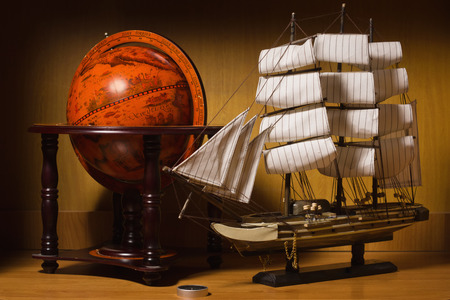 model sailing ship and old globe on a table photo