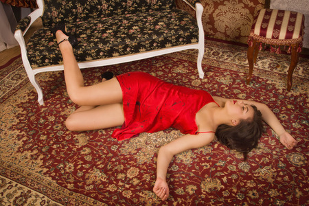 Crime scene simulation. Lifeless woman in a luxurious lingerie lying on the floor photo