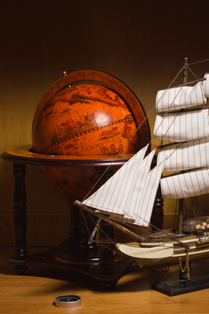 model sailing ship, compass and old globe on a table photo