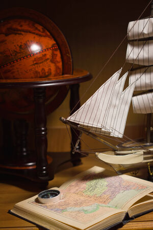 model sailing ship, map book and compass on a table photo