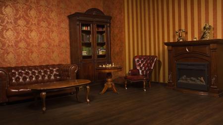 Sala biblioteca classica con poltrona in pelle, tavolo e libreria in legno Archivio Fotografico - 32423374