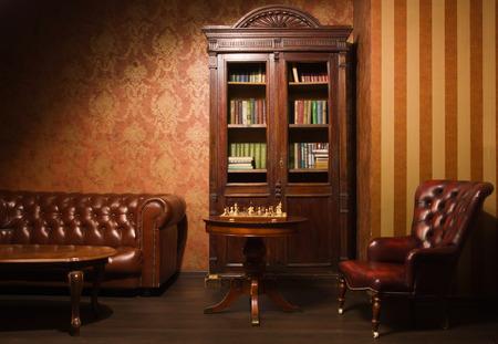 革張りのアームチェア、木製のテーブル、本棚の古典的な図書室