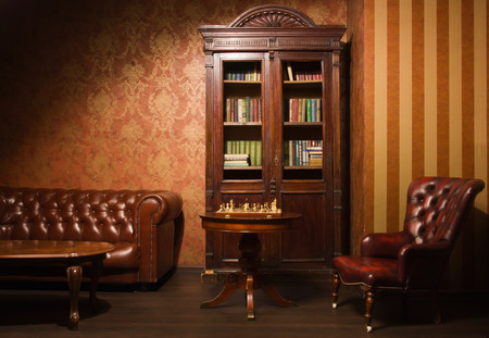 Klassieke bibliotheek kamer met lederen fauteuil, houten tafel en boekenkast