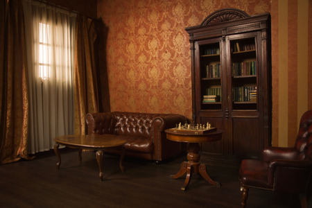 Classical library room with leather armchair, wooden table and bookcase 스톡 콘텐츠