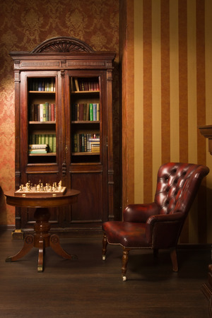 Classical library room with leather armchair, wooden table and bookcase Standard-Bild