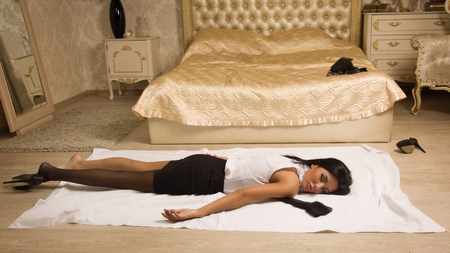 Crime scene simulation. Strangled victim lying on the floor in a luxury bedroom photo