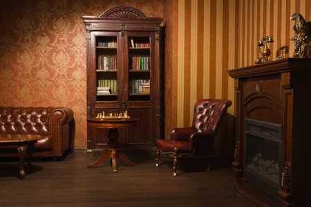 english book: Classical library room with leather armchair, wooden table and bookcase Stock Photo