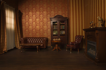 Classical library room with leather armchair, wooden table and bookcase 免版税图像
