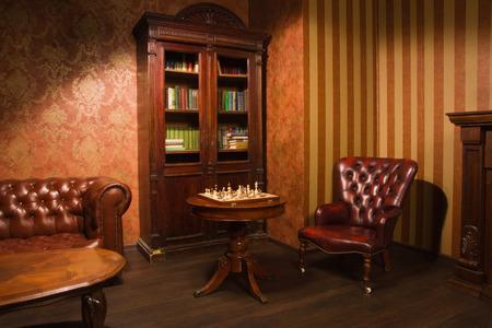 Sala biblioteca classica con poltrona in pelle, tavolo e libreria in legno Archivio Fotografico - 32436253