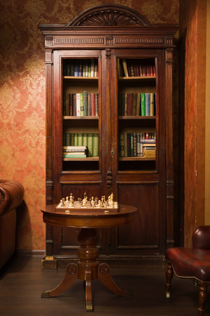 Classical library room with leather armchair, wooden table and bookcase photo