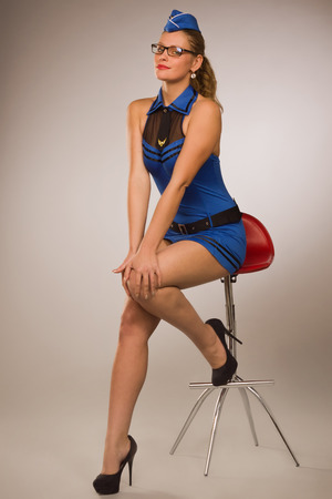 Portrait of sexual stewardess over grey background Stock Photo