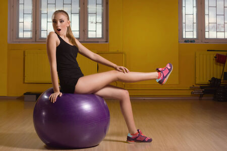 fit ball: Young woman exercising with a fit ball