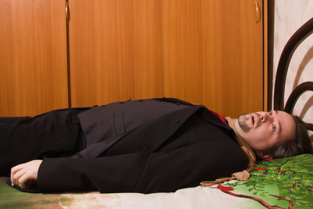 swooned: Corpse of strangled business man lays on a bed Stock Photo