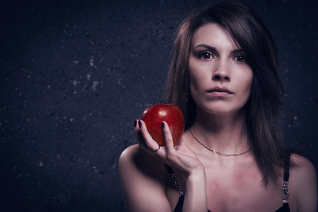 sanitarium: Asylum. Lonely mad woman with red apple. Low key. Stock Photo