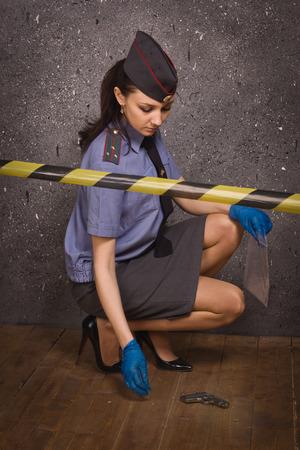 Policewoman criminalist working on a crime scene photo