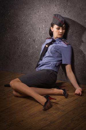 Crime scene imitation. Woman police officer lying on a floor